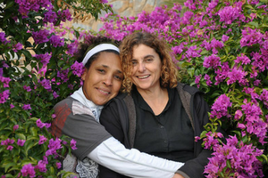 Two females surrounded by purple flowers